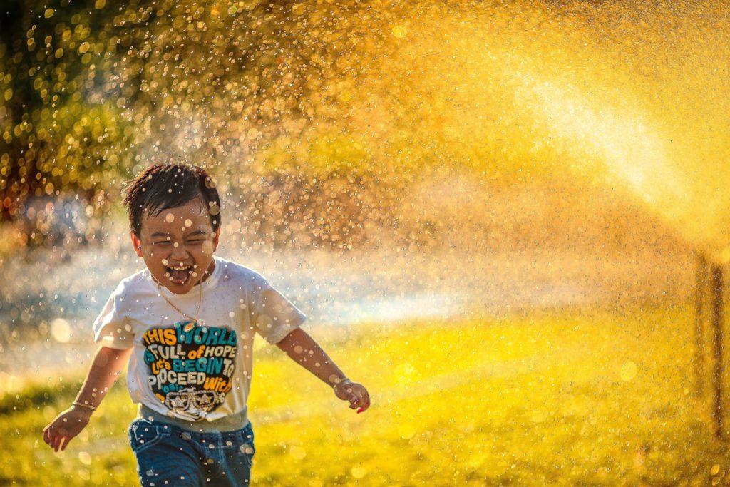 Child playing in sprinkler